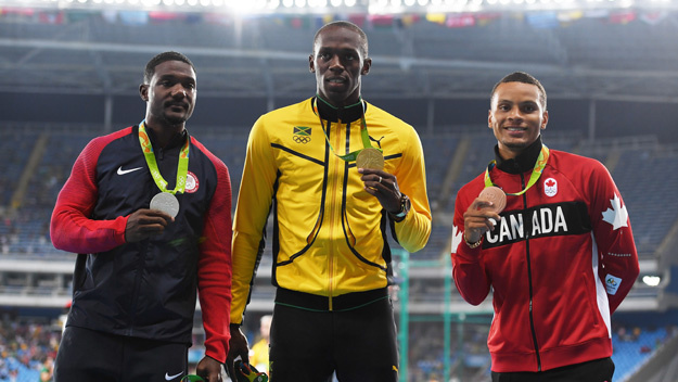 Silver medalist Justin Gatlin, gold medalist Usain Bolt and bronze medalist Andre de Grasse on the podium during medal ceremony for Men's 100 metres (Photo by Shaun Botterill/Getty Images)